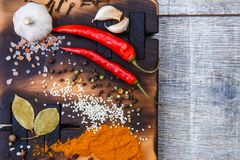 Composition with a cutting board, spices and hot pepper on a wooden background Royalty Free Stock Images