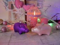 Composition décorative d'une paire de décorations de Noël des porcs, bougies brûlantes, illuminations de fête, coeurs de feutre,  photos libres de droits