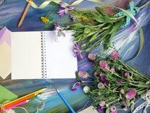 Composition décorative lumineuse des matériaux, du bloc-notes et des fleurs d'art sur un fond bleu crayeux photo libre de droits