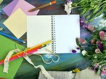 Composition décorative lumineuse des matériaux, du bloc-notes et des fleurs d'art sur un fond bleu crayeux photographie stock
