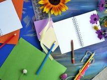 Composition décorative lumineuse des matériaux, du bloc-notes et des fleurs d'art sur un fond bleu crayeux images libres de droits