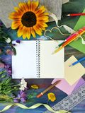 Composition décorative lumineuse des matériaux, du bloc-notes et des fleurs d'art sur un fond bleu crayeux image libre de droits