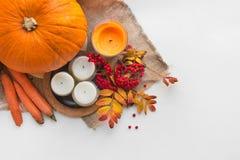 Composition d'automne des potirons, des feuilles, des baies et des bougies Image stock