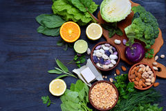 Composition on a dark background of products containing folic acid, vitamin B9 - green leafy vegetables, citrus, beans, peas, nuts. Yeast. Top view. Flat lay stock images