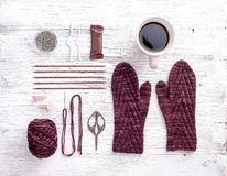 Composition with dark red mittens. Knitting yarn, knitting needles and accessories on a wooden background, top view. Knolling knitting Royalty Free Stock Images