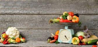 Composition de bannière des légumes frais organiques crus, équilibre sur la table brune en bois photo libre de droits