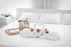 Composition de deux cygnes de serviette, fleurs et seaux à glace avec le champagne sur le lit Photo libre de droits