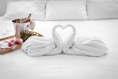 Composition de deux cygnes de serviette, fleurs et seaux à glace avec le champagne sur le lit Photos stock