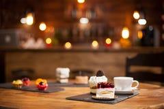 Composition de différents gâteaux avec des saveurs savoureuses au-dessus d'une table en bois dans un café photos stock