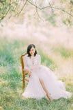 Composition de gisement de ressort de la femme dans la longue robe blanche se reposant dans la vieille chaise moderne Photos libres de droits