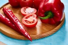 Composition de groupe et de moitiés de tomate et poivron doux de plat en bois, vue supérieure, plan rapproché, foyer sélectif Images libres de droits
