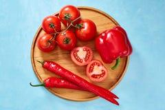 Composition de groupe et de moitiés de tomate et poivron doux de plat en bois, vue supérieure, plan rapproché, foyer sélectif Photographie stock libre de droits