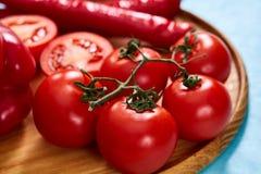 Composition de groupe et de moitiés de tomate et poivron doux de plat en bois, vue supérieure, plan rapproché, foyer sélectif Photographie stock