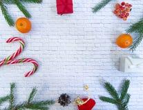 Composition de Noël Cadeau de Noël, cônes de pin, branches impeccables sur un fond de blanc de brique Vue plate et supérieure Photographie stock libre de droits