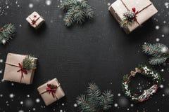 Composition de Noël Cadeaux de Noël ou de nouvelle année et brindilles de sapin sur un fond noir Copiez l'espace, configuration d Photos libres de droits