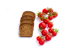 Composition de pain noir et groupe de tomates-cerises Image libre de droits