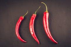 composition de peppe de piment sur une pierre foncée/poivre d'un rouge ardent du Chili sur un fond en pierre foncé Vue sup?rieure photographie stock