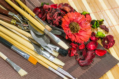 Composition of decorating flowers and leaves, spatula and brushes on a table Royalty Free Stock Photography