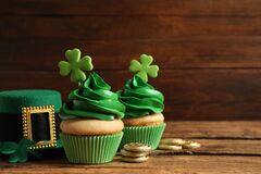 Composition with delicious decorated cupcakes on table, space for text. St. Patrick`s Day celebration