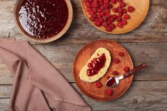 Composition with delicious raspberry jam on wooden table, top view. Beautiful composition with delicious raspberry jam on wooden table, top view Royalty Free Stock Image