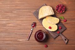 Composition with delicious raspberry jam on wooden table, top view. Beautiful composition with delicious raspberry jam on wooden table, top view Royalty Free Stock Photography