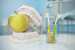 Composition. Denture, apple and toothbrushes in glass Royalty Free Stock Images