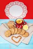 Composition des biscuits, de la tasse de thé, des écrous et du citron sur le fond de vintage Concept d'amour Photo stock