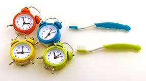Composition des brosses à dents et des horloges colorées Photographie stock