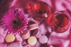 Composition des fleurs, des bonbons et du vin sur un fond rose Photos stock