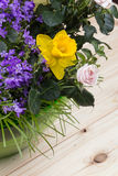 Composition des fleurs et de l'herbe de ressort dans un bol en verre vert sur un fond en bois clair avec le grain évident Photos libres de droits