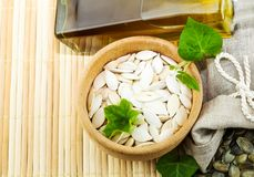 Composition des graines de citrouille et de l'huile de potiron Photos stock