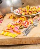 Composition des pâtes colorées de ravioli, du plat blanc, de deux fourchettes et d'un tamis sur une toile images stock