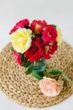 Composition des roses colorées dans un vase sur une serviette en osier sur un fond blanc image stock