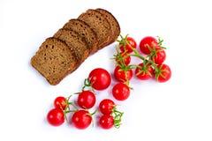 Composition des tranches de pain noir et groupe de tomates Photo stock