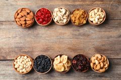 Composition of different dried fruits and nuts on wooden background, top view. Space for text stock image