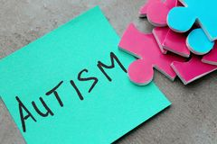 Composition of different puzzles and sticker. With word AUTISM on grey background Royalty Free Stock Photos