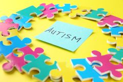 Composition of different puzzles and sticker with word AUTISM. On color background Royalty Free Stock Photos