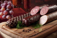 A composition of different sorts of sausages. On dark background Royalty Free Stock Photos