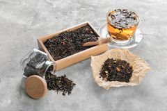 Composition with different types of dry tea leaves on grey background stock photography
