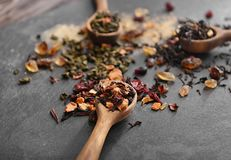 Composition with different types of dry tea leaves and spoons on slate plate royalty free stock photo