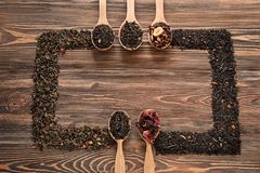 Composition with different types of dry tea leaves on wooden background stock photo