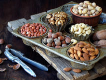A composition from different varieties of nuts on a wooden background - almonds, cashews, peanuts, walnuts, hazelnuts, pistachios. Royalty Free Stock Images