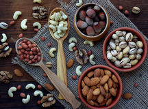 A composition from different varieties of nuts on a wooden background - almonds, cashews, peanuts, walnuts, hazelnuts, pistachios. A composition from different Stock Photos