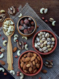 A composition from different varieties of nuts on a wooden background - almonds, cashews, peanuts, walnuts, hazelnuts, pistachios. A composition from different Stock Photography