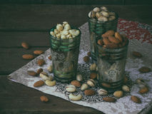 A composition from different varieties of nuts on a wooden background - almonds, cashews, pistachios. Royalty Free Stock Image