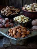 A composition from different varieties of nuts on a wooden background - almonds, cashews, walnuts, hazelnuts, pistachios. Royalty Free Stock Photo