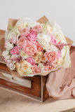 Composition of different varieties  roses. florist did rich bunch flowers light background, wooden surface. green vase Royalty Free Stock Photo