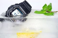 Composition of digital wristwatch, lemon and mint in ice cube Royalty Free Stock Photos