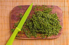 Composition with dill on a board with a knife on a bamboo mat. Chopped dill on a board with a green knife on a bamboo mat Royalty Free Stock Images