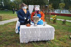 The composition of the dolls. Man and woman drinking tea from a samovar in nature. Russia. Royalty Free Stock Photos